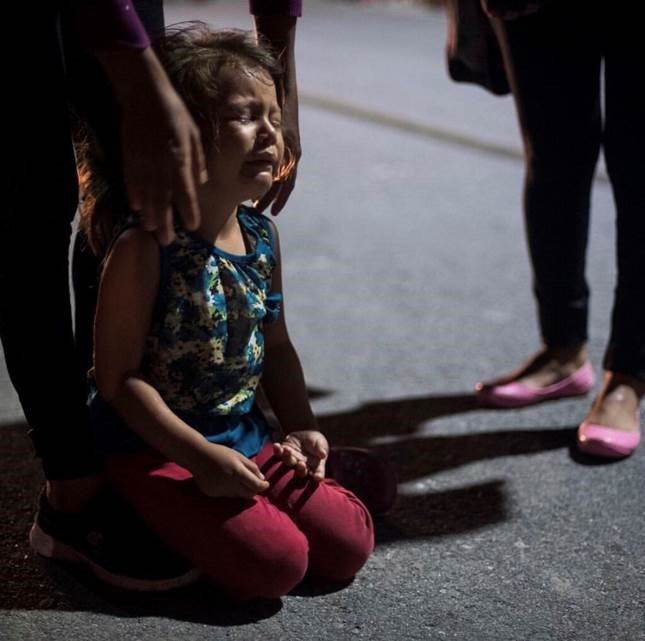 A 4-year-old girl collapses from exhaustion and refuses to walk any further.   Powerful photo from the caravan by .