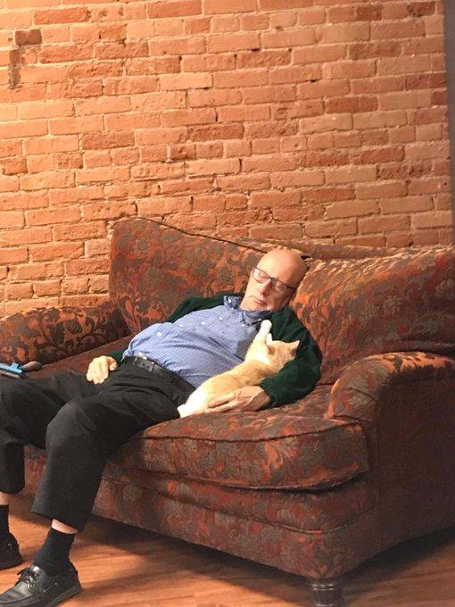 ソファーに座ったまま居眠りしてるおじいさん ネコは腕の中にもぐりこんで甘えてる