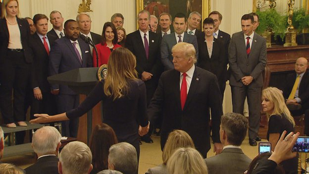 Mrs Trump stops her husband from heading out of the East Room, reminding him he needed to sign the opioid treatment and prevention bill.