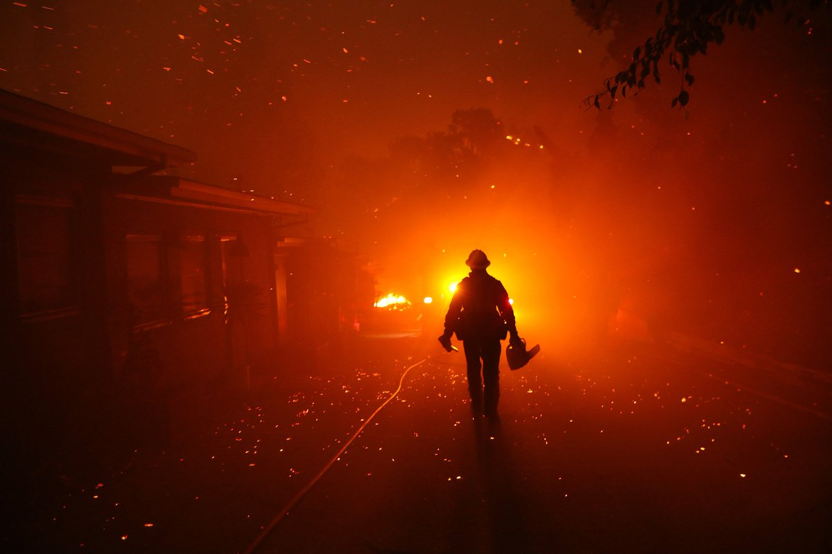 A firefighter walks towards his engine after trying to prevent the Woolsey Fire from overtaking structures in Malibu lat.ms/2RQ2jox