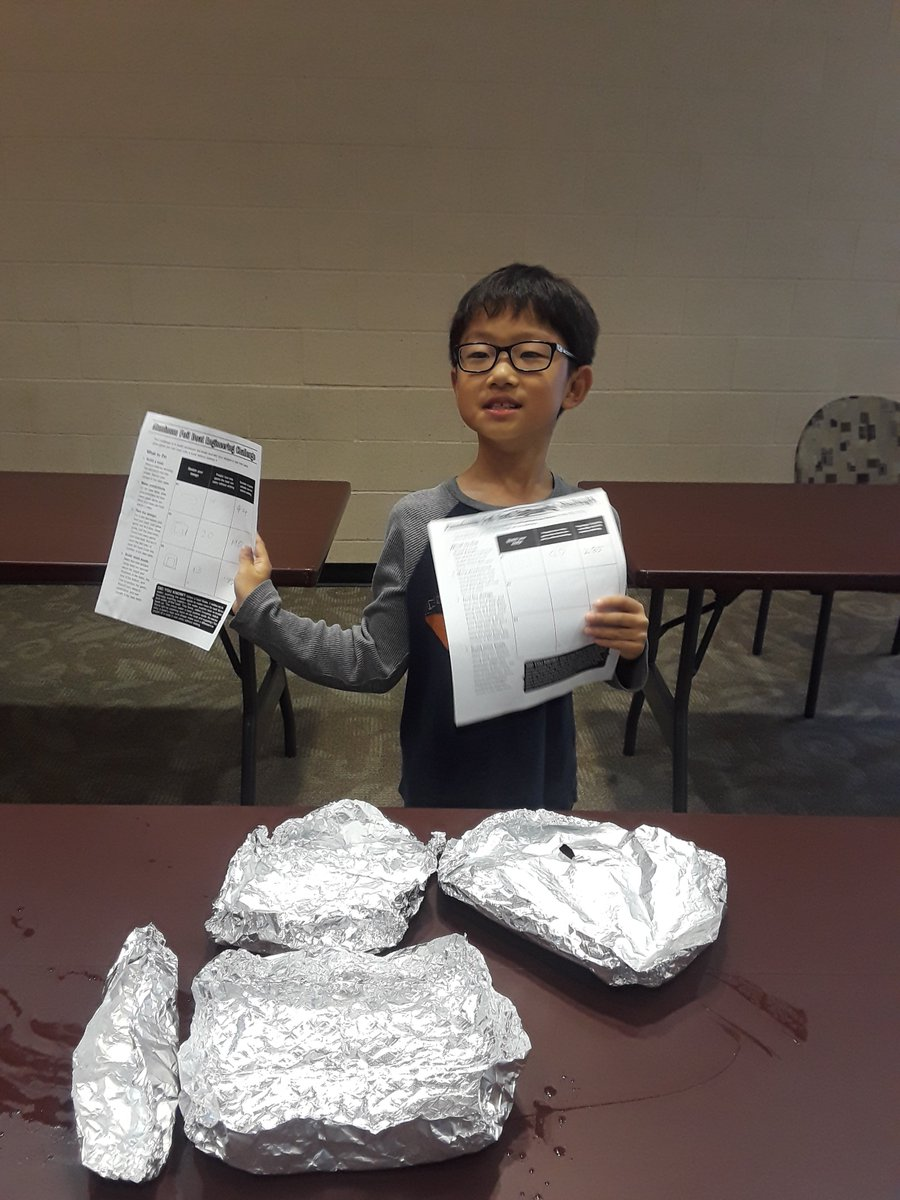 OCOB Foil Boat Challenge - Child with glasses holding directions in front of foil boat