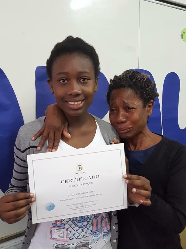 Eloá, aluna da escola pública, ganhando um prêmio de destaque no Sarau Literário. A emoção da mãe é nossa emoção. A alegría de Eloa, é nossa alegria.  Brasil, 2018.