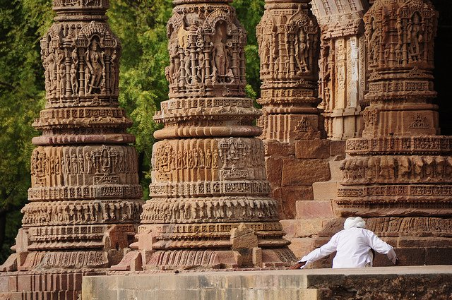 Details of intricately carved pillars flanking Sopāna(stairs) leading to Mandapa from Surya Temple in Modhera(Gujrat) Dated: ~10th century CE or older As usual here base moulding is Padma and lower portion of column follows staggered square plan, each face depicting gods. Photo