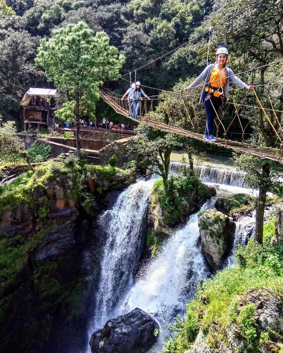 Visitantes caminando por el puente colgante en Quetzalapan