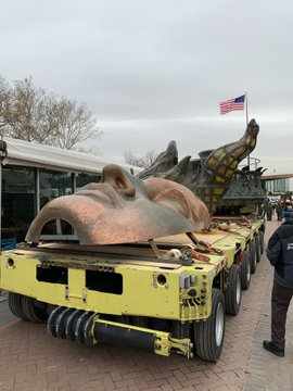 The replica face of the Statue of Liberty with the torch are on a trailer that moved them across Liberty Island.