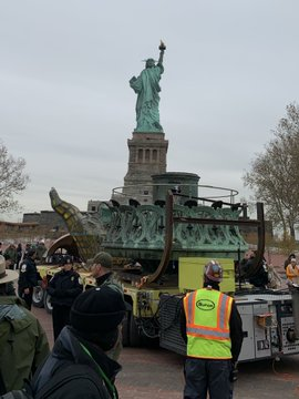 The replica face of the Statue of Liberty with the torch are on a trailer that moved them across Liberty Island. The Statue of Liberty is in the background.