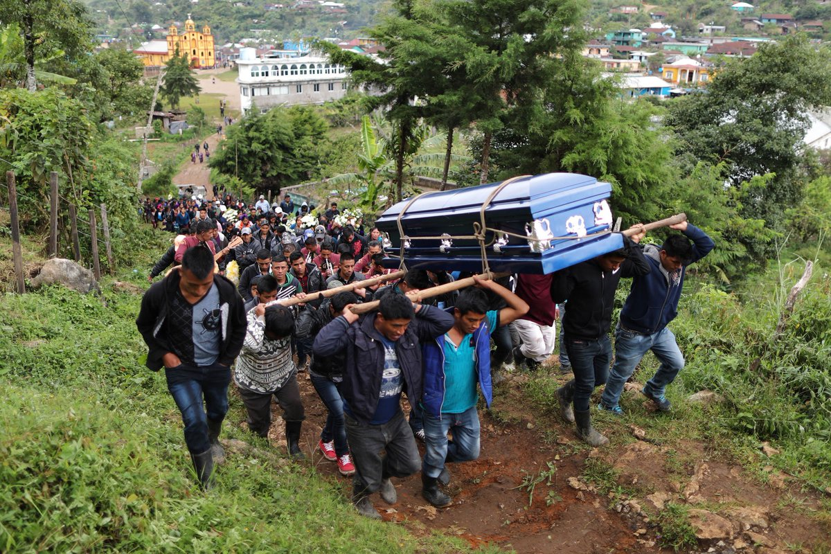 10/12 In Aguacate, some 250 people met the ambulance transporting Paiz's body. They stood in ankle-deep mud and pouring rain as eight men lifted his coffin out and took it into the family home.