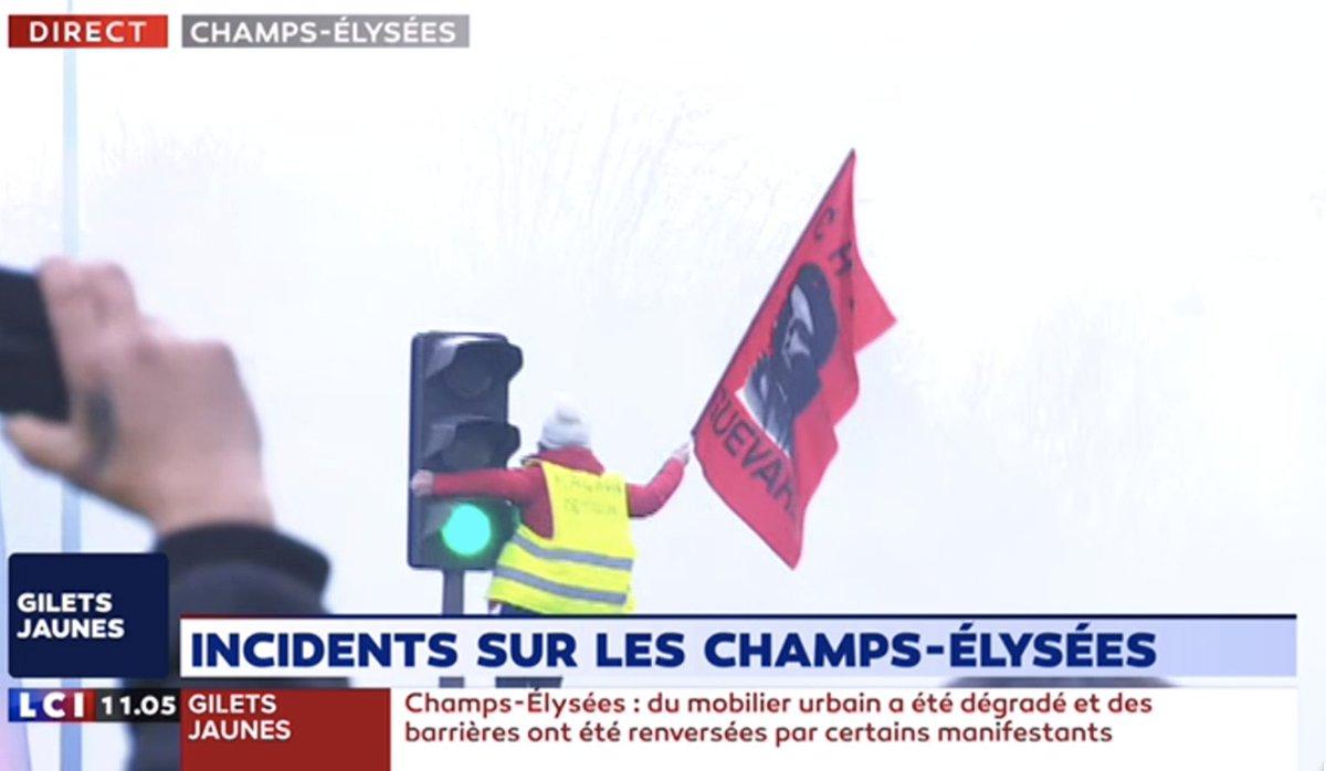 🇫🇷 Une gilet Jaune brandit un… drapeau Che Guevara au milieu des affrontements au niveau du rond point des Champs Elysées