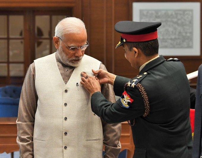 On the occasion of #ArmedForcesFlagDay officers of Kendriya Sainik Board, MoD pinning a flag on PM @narendramodi ji Photo