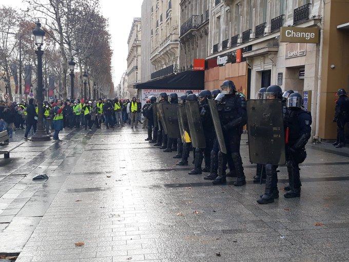 Quelques tensions et tirs de projectiles sur le haut des Champs. Ici, un groupe de CRS encerclé devant une boutique orange. #8Decembre Photo