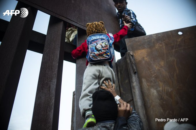 Central American migrants climb a barrier separating Mexico and the US at Playas de Tijuana before being detained by watching US Border Patrol agents 📷Guillermo Arias and Pedro Pardo Foto