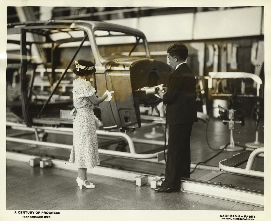 Via the UIC Library Digital Collection: Miss Gladys Farkes, 27 years old and 47 inches tall, watches while Victor Bump, 27 years old and 50 inches tall, works on the Chevrolet Assembly line in the General Motors Building at the Worlds Fair. #vintagechicago #transportationtuesday