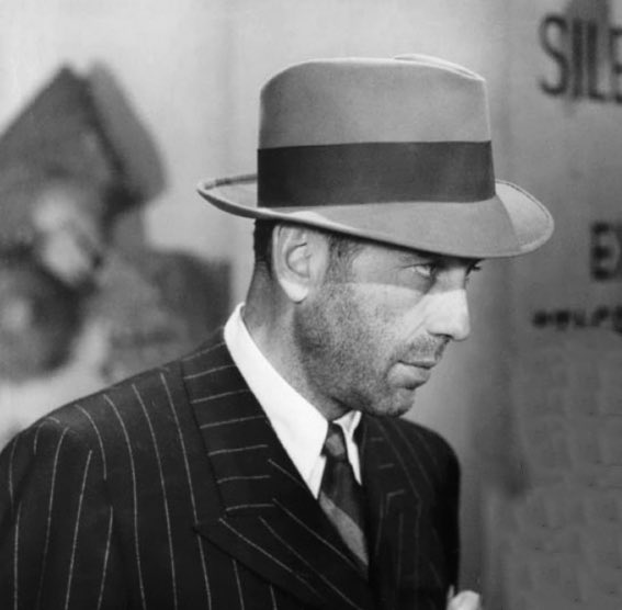 A nice photo of Humphrey Bogart with a sharp suit, stubble, and fedora.