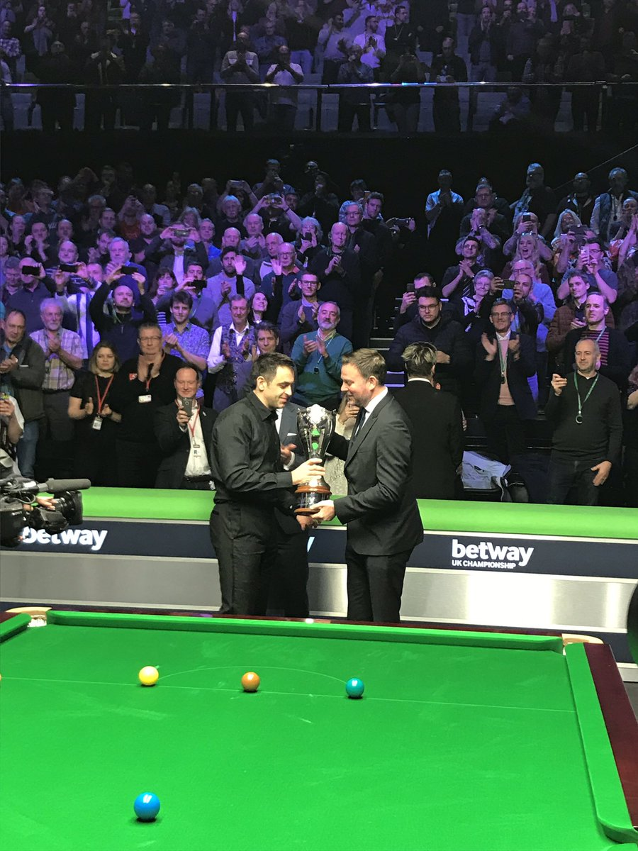 Ronnie O'Sullivan is presented with the 2018 @betway UK Championship title by @Alan_Alger_.