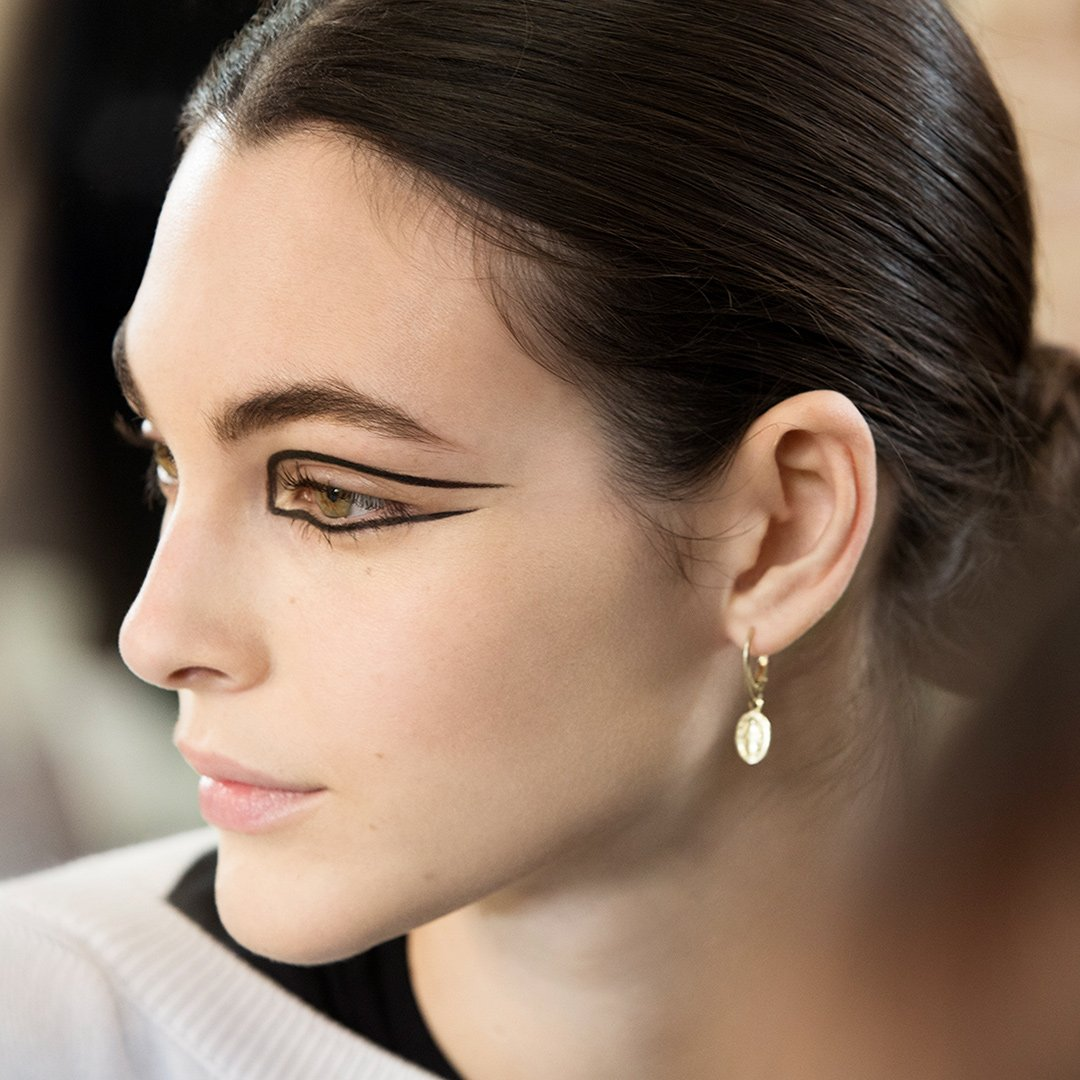 A makeup closeup backstage — Global Creative Makeup and Colour Designer of the House, Lucia Pica created an abstract look for the Paris-New York 2018/19 Métiers d'art show. Focus was on the graphic eyes outlined in bold colours.