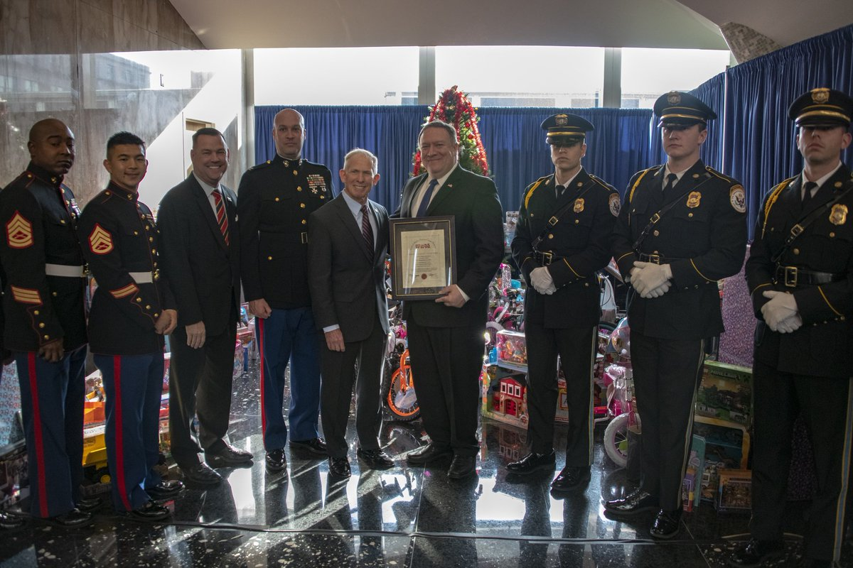 U.S. Secretary of State Michael R. Pompeo poses for a photo with U.S. Marines after being presented with a plaque of appreciation for the Department during the Toys for Tots ceremonial presentation event to the Marine Corps Reserve at the U.S. Department of State in Washington, D.C. on December 10, 2018. [State Department photo by Ron Przysucha/ Public Domain]