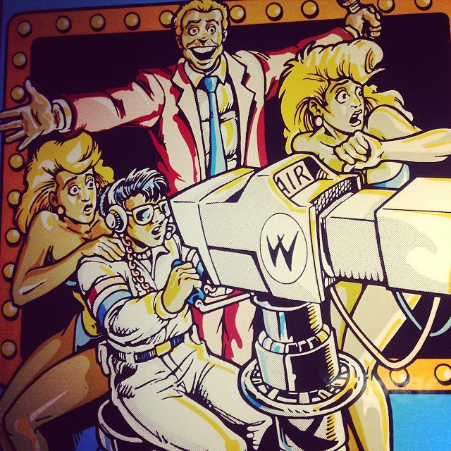 Detail of the arcade marquee of 1989s Smash T.V., featuring art by future Mortal Kombat co-creator John Tobias