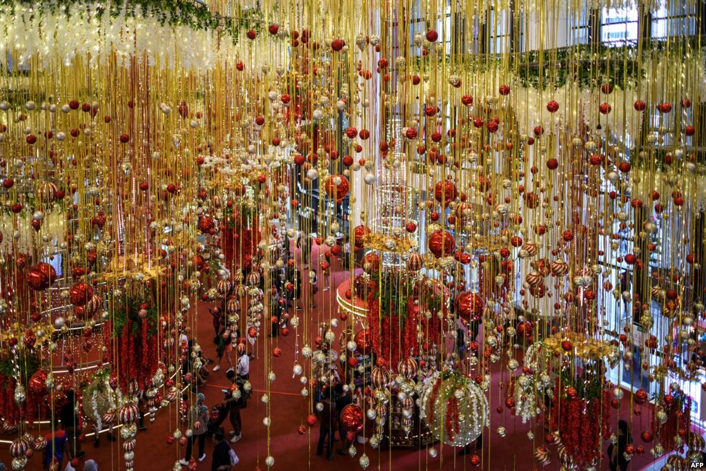 People walk at a shopping mall filled with Christmas decorations in Kuala Lumpur, Malaysia - AFP/VoA