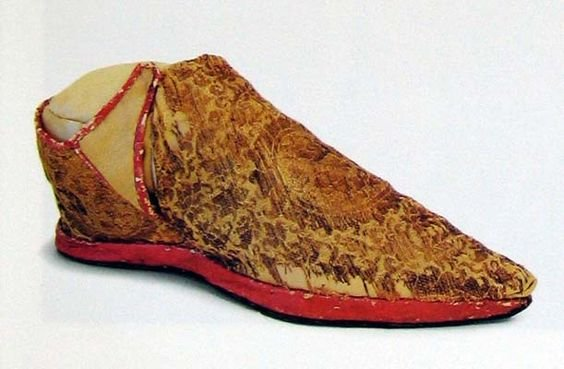archival photograph of a jacquard woven fabric shoe with red sole and trimmings. The top