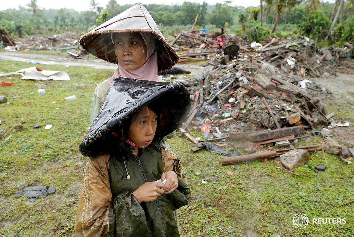 A woman and child are seen next to debris after a #tsunami in #Sumur Banten province, #Indonesia December 26, 2018. REUTERS/Jorge Silva