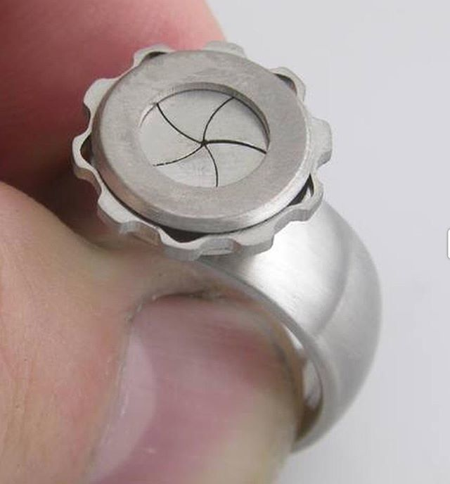 78b01dbe34e This ring is called Iris. Made from aerospace grade titanium and laser cut  and laser welded. The mechanical shutter closes to protect the sto… ...