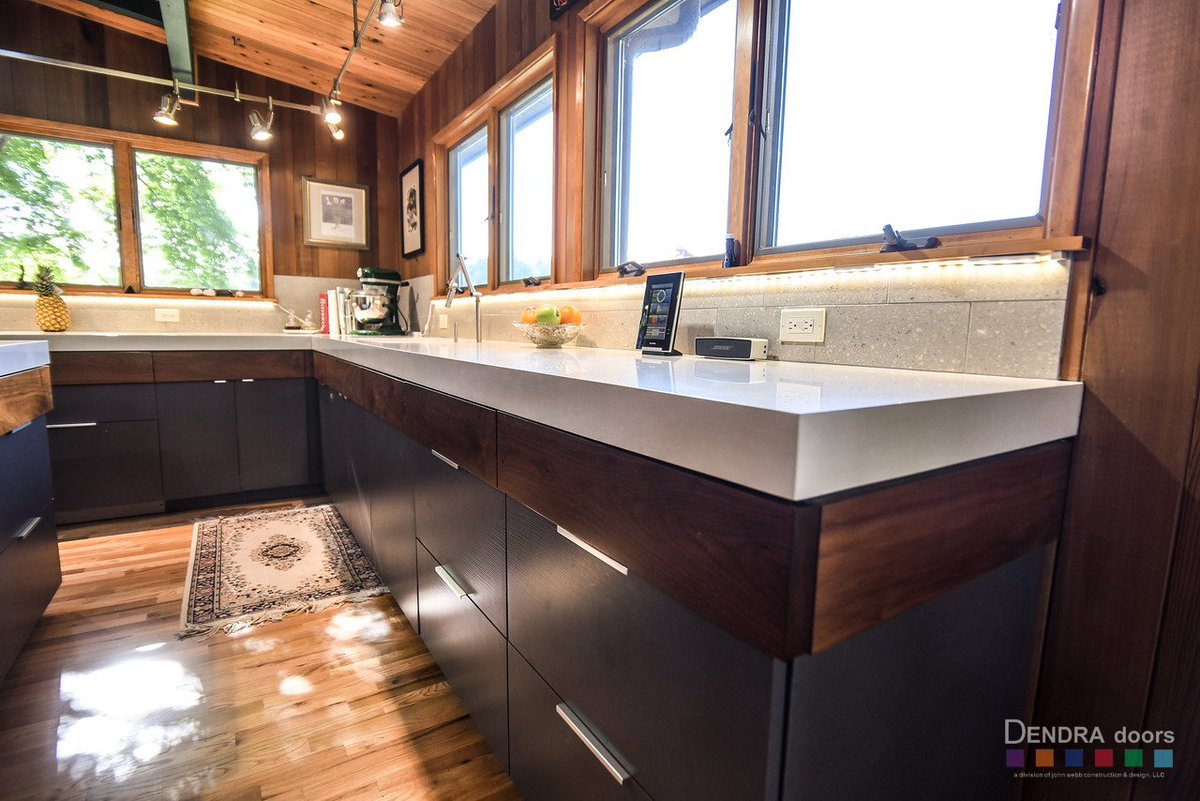 These concrete colored slab style doors mixed with our walnut veneer makes the space feel completely modern and very natural kitchen design by