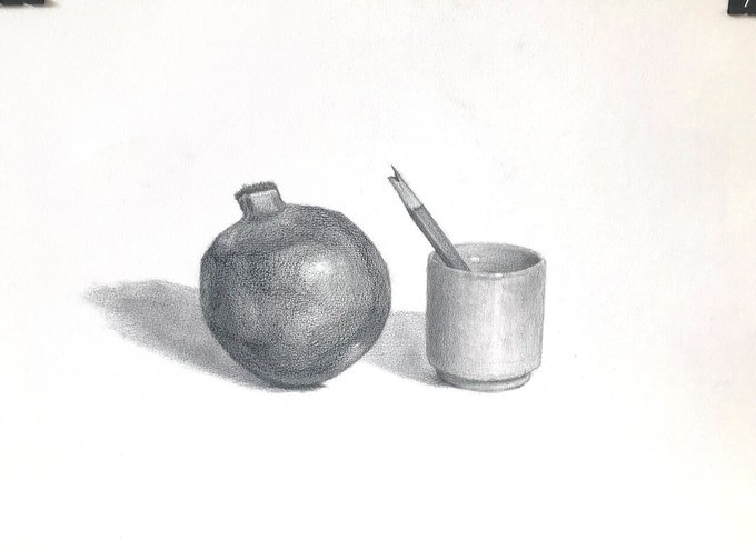 ザクロと先の折れた鉛筆を入れた器