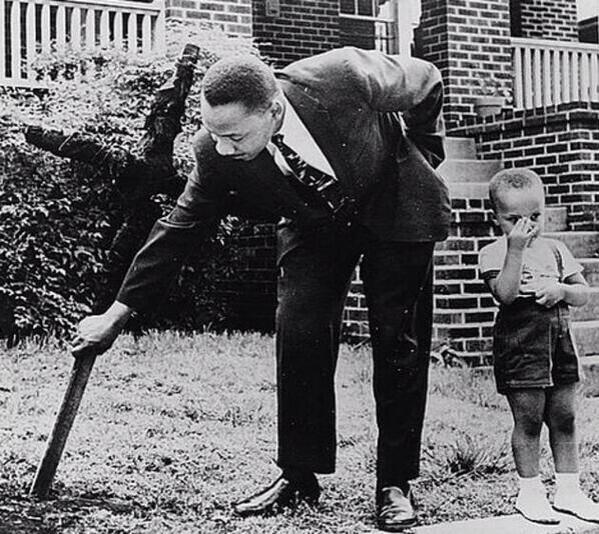 MLK (90th birthday today) pulling burnt cross from his lawn in presence of his son, Atlanta, 1960