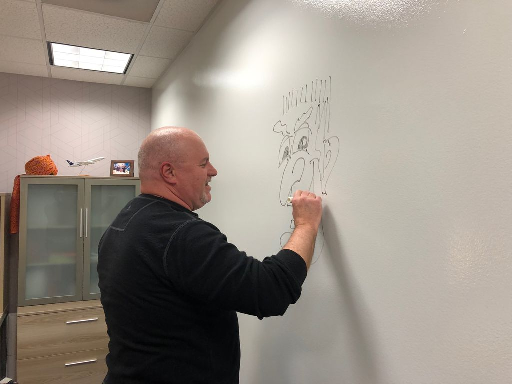 Our very own @DaveShurte - senior graphic #designer initiates the enormous marker board wall in my new office! Great work Dave! #ExperienceECI @exhibitconcepts