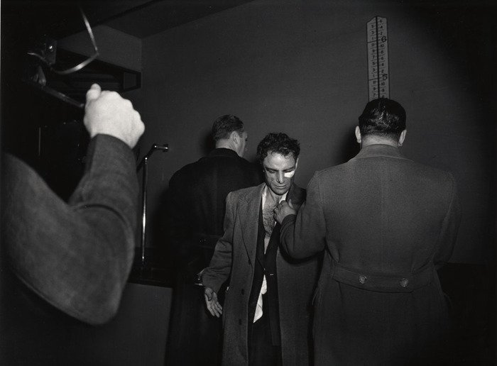 """Weegee at the precinct, armed with his trusty Speed Graphic camera. """"He looked like a stubborn surly, snarling animal,"""" wrote Weegee. """"He stumbled and sagged over to one side, like a drunk."""" https://bit.ly/2hPymoq 📷 Weegee, New York, 1941 #WeegeeWednesday"""