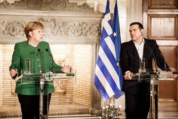 Kanzlerin Merkel steht neben Griechenlands Ministerpräsident Tsipras und spricht bei einer Pressekonferenz ins Mikrofon.