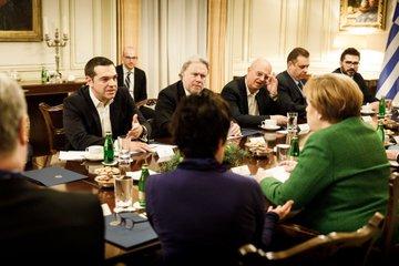 Griechenlands Ministerpräsident Tsipras unterhält sich über einen Tisch hinweg mit Kanzlerin Merkel.