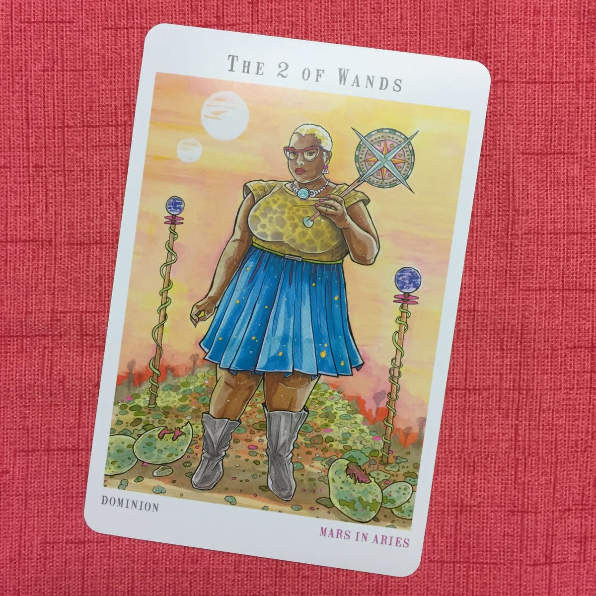 Next World Tarot - Two of Wands - A Black femme in a blue skirt and a leopard print top, with close-cut hair, holds a mace in her left hand and regards the reader through cat-eye glasses.