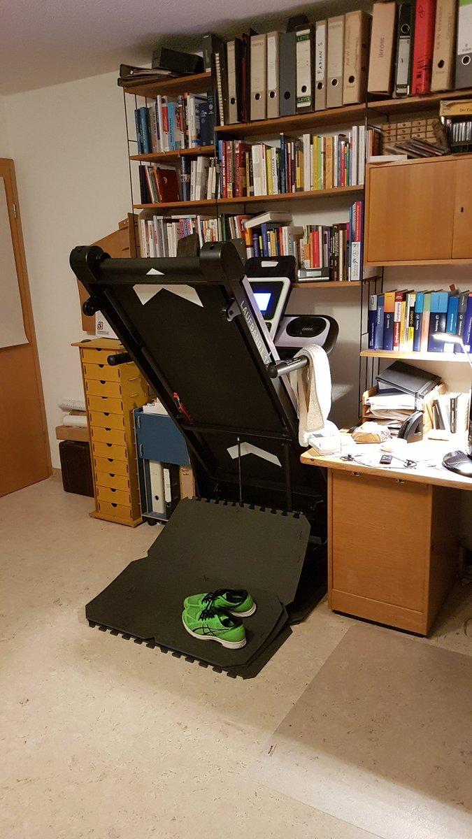 Laufband in einem Zimmer vor der Bücherwand, hochgeklappt mit grünen Laufschuhen darunter.