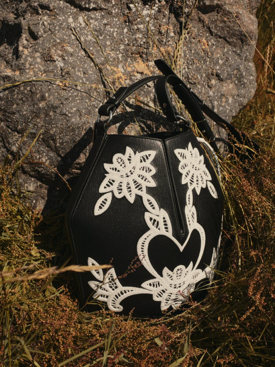 A black and ivory Victorian-inspired broderie anglaise embroidered bucket bag. From the Alexander McQueen Spring/Summer 2019 pre-collection. Explore: https://t.co/I8V0bm7YJg #McQueenPreSS19 #AlexanderMcQueen