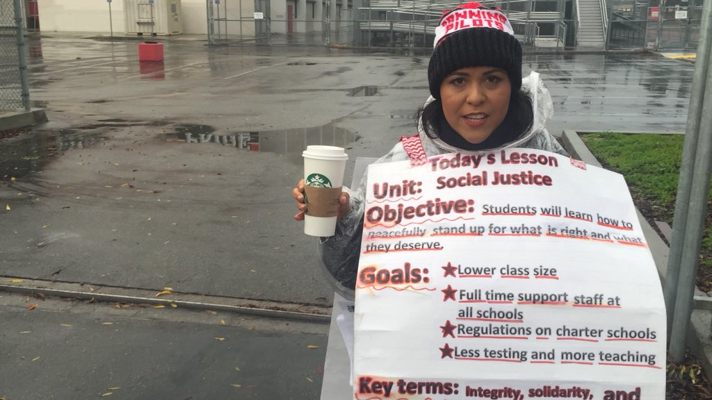"""Banning High English teacher Lucia Rodriguez, holding the venti white mocha a student brought her, wearing her self-laminated sandwich board. """"I should have put 'lesson for the week.'"""" #LAUSDstrike"""