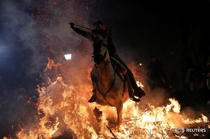 Revelers ride their horses through smoke and flames to purify their animals during the Luminarias celebration in Spain. More photos: https://reut.rs/2RO3GIc  📷 Susana Vera