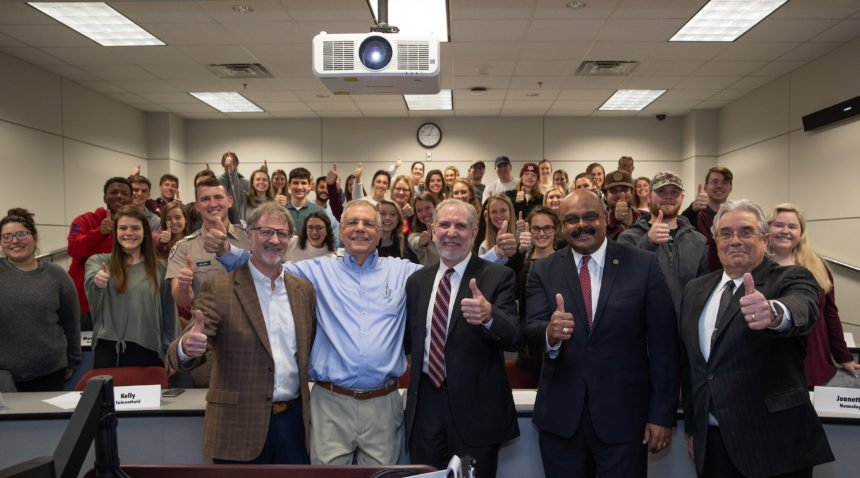Dr. Busch with president young and dean eli jones in front of the class room