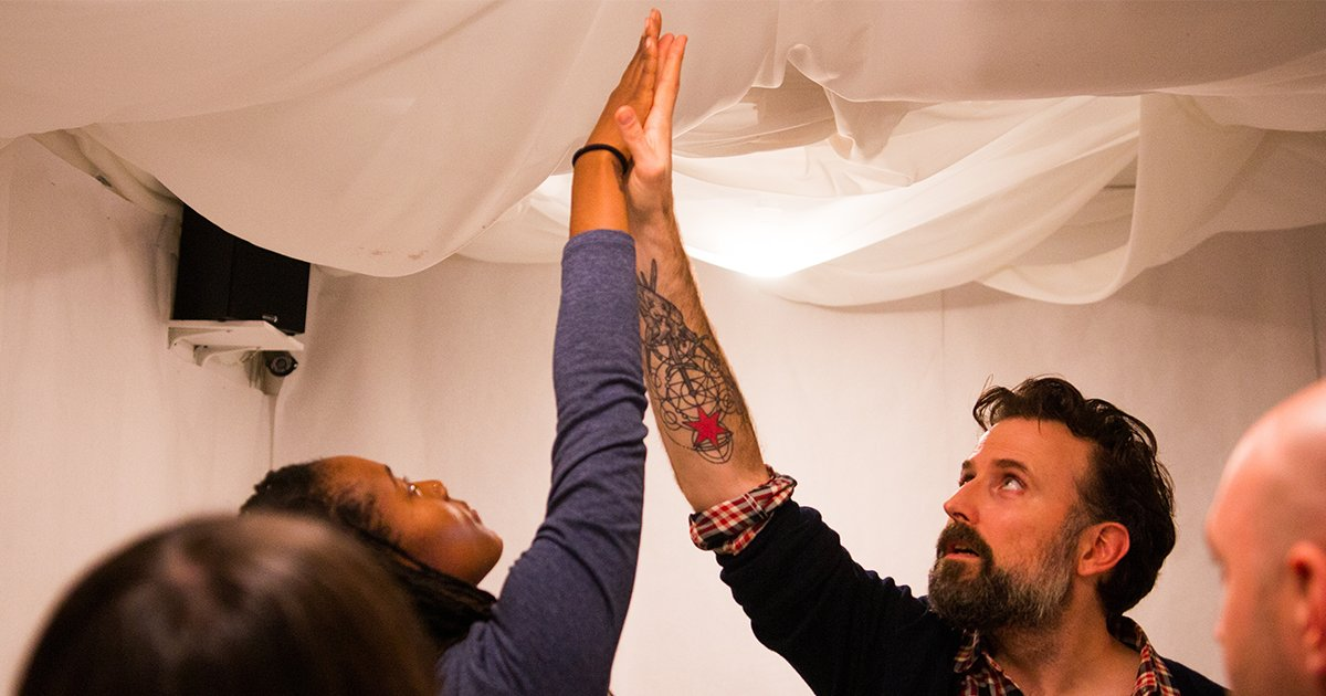 Woman and Man with hands in the air as their palms meet.