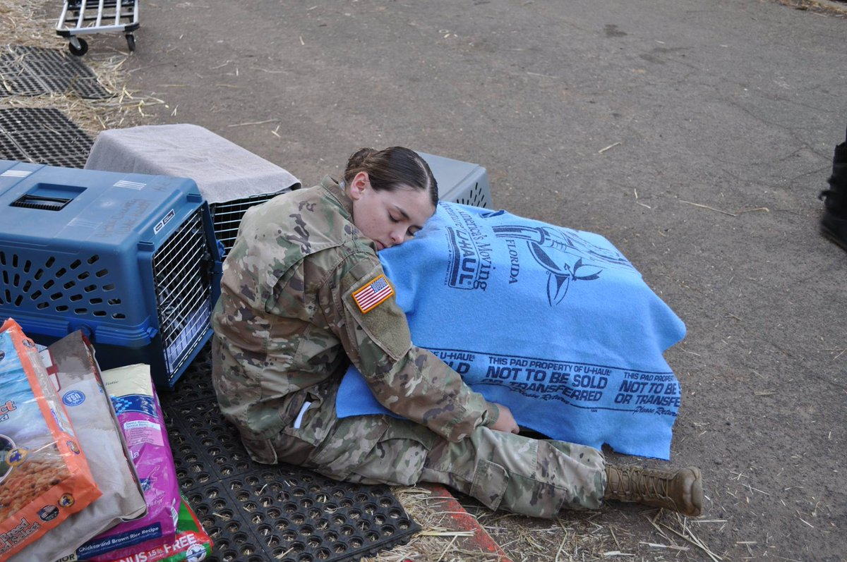 A woman in fatigues hugging an animal cage with an animal in it