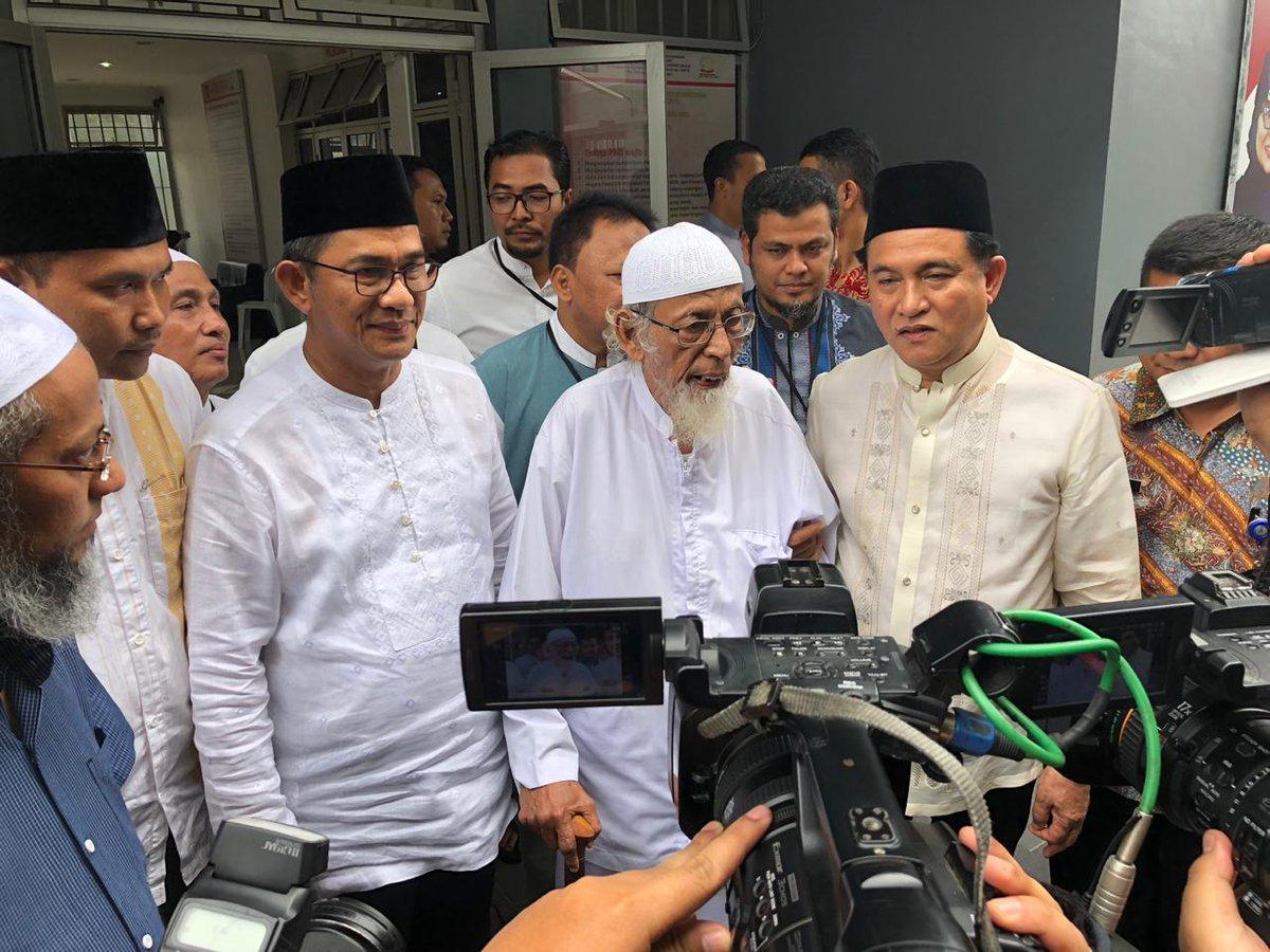 Abu Bakar Baasyir digandeng lengannya oleh Yusril Ihza Mahendra saat bertemu awak media