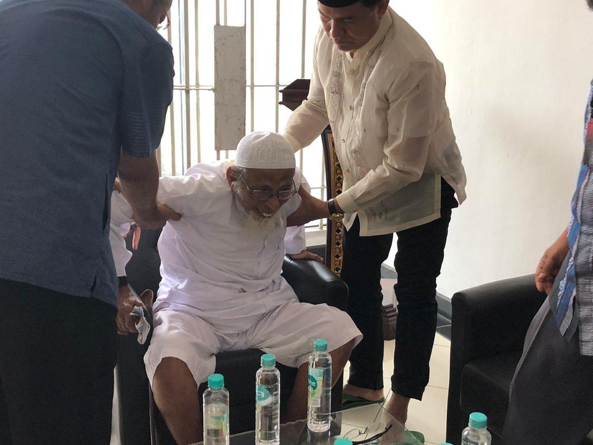 Abu Bakar Baasyir dibantu saat akan berdiri dari tempat duduk