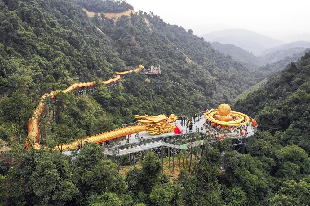 In pics: a 99-meter-long dragon dancing on the glass walkway of world's longest dragon sculpture flying over the mountain in Qingyuan, Guangdong Province