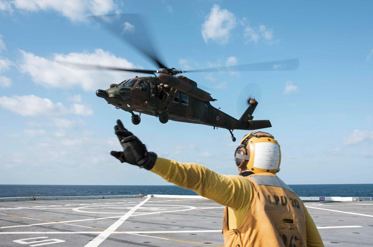 .@USNavy Petty Officer 3rd Class Dion Sanders signals to a UH-60 Black Hawk helicopter on the flight deck of #USSGreenBay in the Philippine Sea.