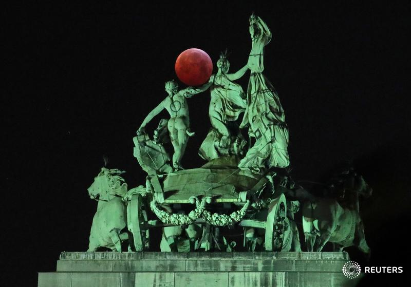 The Super Blood Wolf Moon is seen on top of the Cinquantenaire arch during the total lunar eclipse in Brussels, Belgium, and more photos of the day: https://reut.rs/2sFhW7O  | 📷 Yves Herman