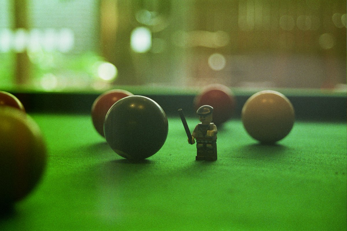 Mini M playing some pool at the pub.... I think he is going to need a bigger cue than that.  Taken with the Minolta X300 and 200 ISO colour expired film.  #photography #lego #photooftheday #pub #pool #legophoto #legophotography