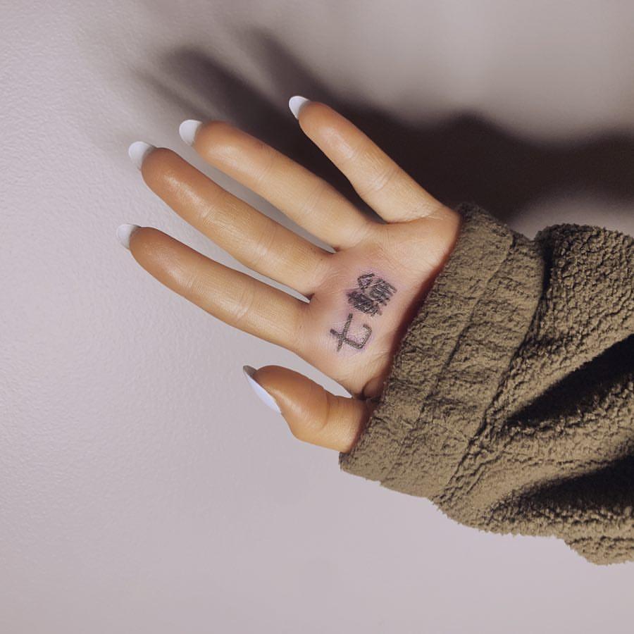 """SOCORRO! Ariana Grande faz tatuagem em japonês para """"7 rings"""", mas acaba errando na grafia e significado se altera totalmente"""