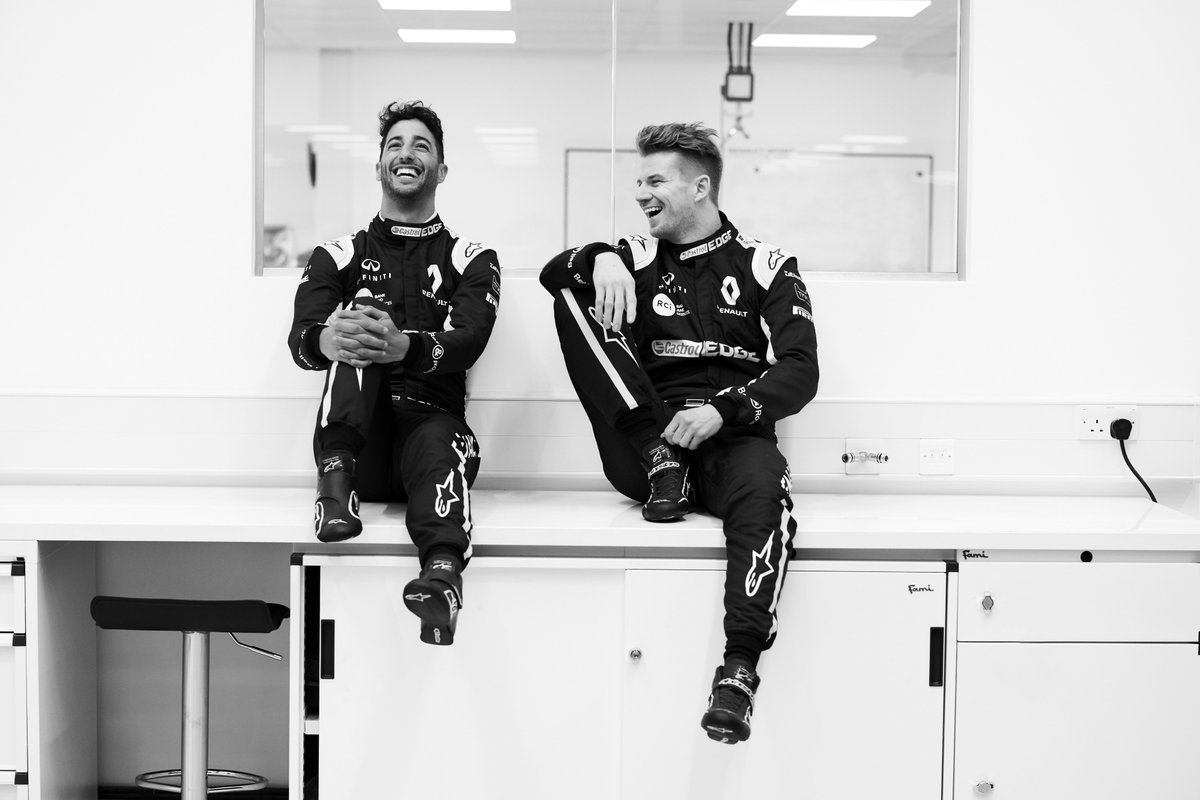 Daniel and Nico in overalls, sitting in the race bays at Enstone. They're laughing and look totally cool.