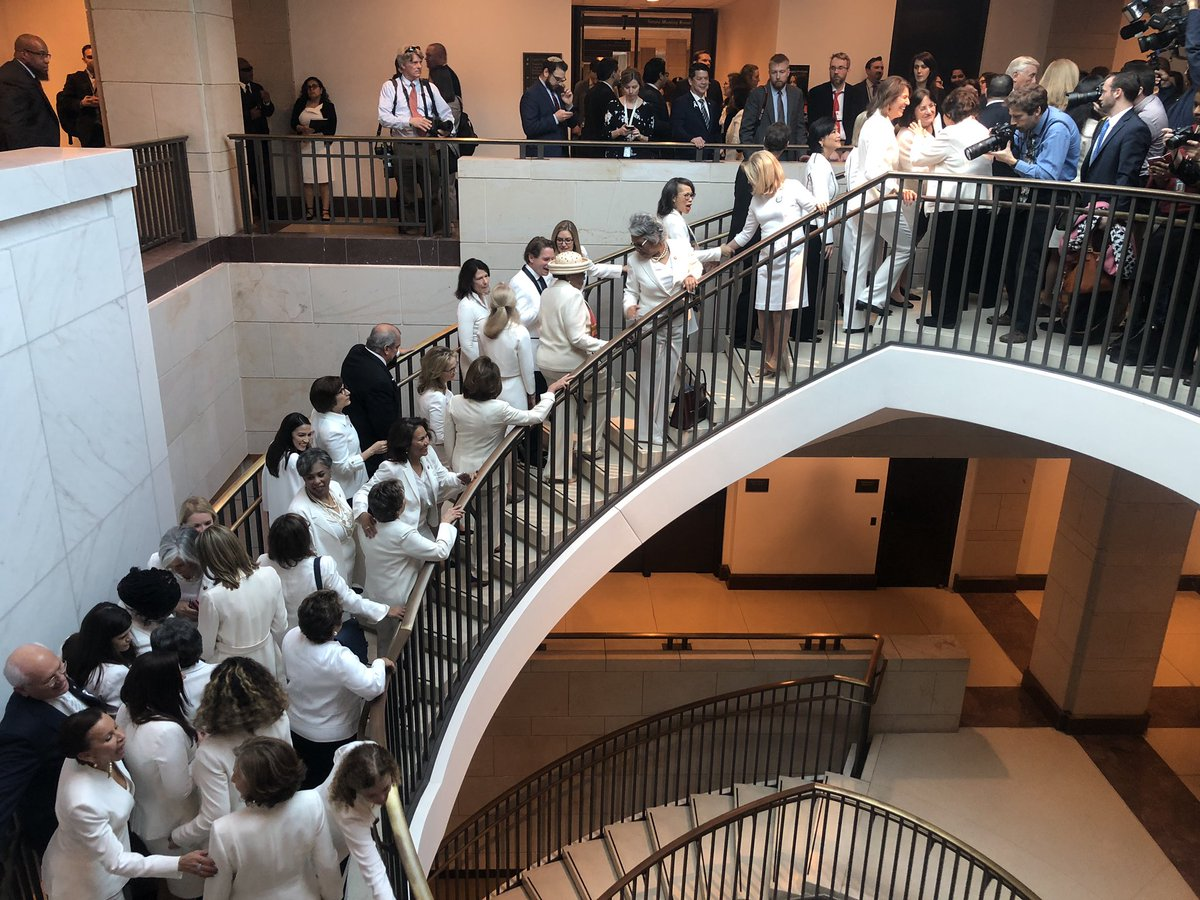 House Democratic women dressed in white for the #SOTU walk up the spiral staircase in the HVC —>