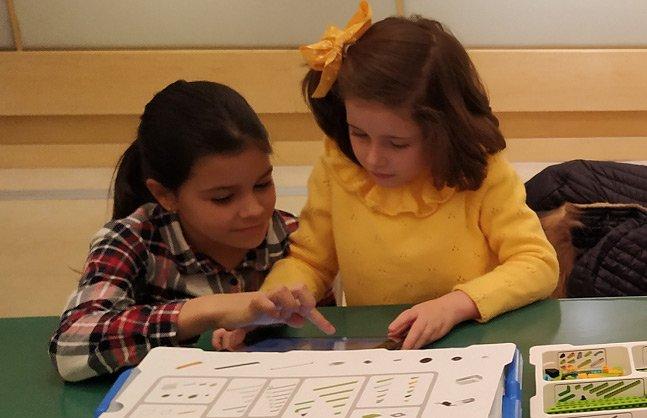 Dos niñas montando un vehículo espacial robotizado con piezas lego.